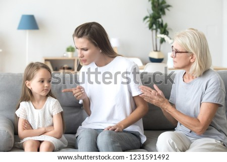 Angry young mother scolding child daughter while old grandmother interfering when strict mom lecturing little girl, three generations disagreements affecting upbringing kid, family conflicts concept