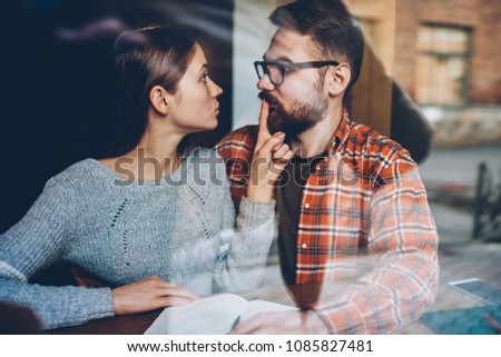 Angry young woman making him stop talking during quarrel.Hipster girl told secret to boyfriend inn and showing shh sitting in coworking space.Bearded man under pressure of girlfriend