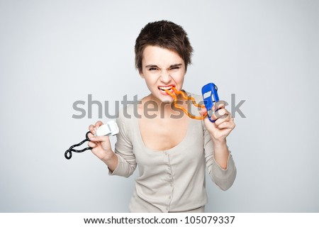 Angry young woman squeezing anti-stress toys