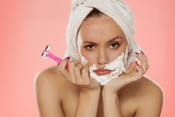 Angry young woman with foam on the face and a razor in her hand