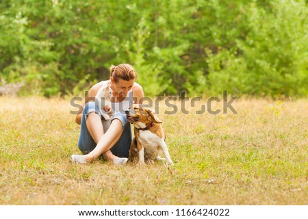 Animal lover woman animal lover sitting on grass with her pets