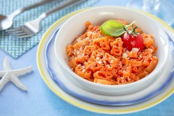 Animal shape pasta with tomato sauce for kids garnished with a fresh ripe cherry tomato and a leaf of basil served on a white plate