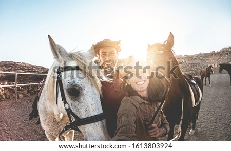 Animals lovers couple taking selfie with horses during sunny day inside ranch corral - Happy people having fun during wild vacation tour - Love, concept - Focus on guys faces
