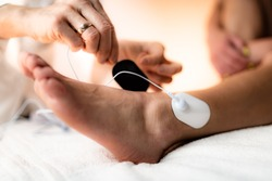 Ankle Joint Physical Therapy with TENS Electrode Pads, Transcutaneous Electrical Nerve Stimulation. Therapist Positioning Electrodes onto Patient's Ankle Joint