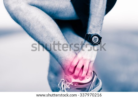 Ankle leg pain, man holding sore and painful foot muscle, sprain or cramp ache filled with red pink bright place. Overtrained injured person when training exercising or running outdoors.