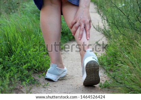 Ankle sprain, woman grabbed her leg while walking on a summer nature. Concept of tired legs, injury on running