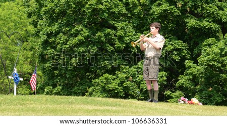 ANN ARBOR, MI - MAY 27: An unidentified boy scout plays taps at the annual Memorial Day observance on May 27, 2012 at Arborcrest Memorial Park in Ann Arbor, MI