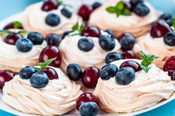 Anna Pavlova dessert with cherries, blueberries and mint, concept of love sweet
