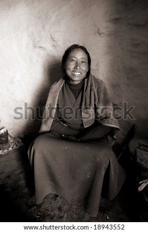 Annapurna Circuit, Nepal - March 2008. Traditional gurung woman in her kitchen and house