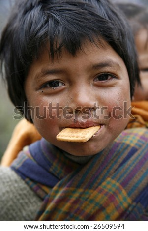 ANNAPURNA, NEPAL - MARCH 20: Portrait of a young boy asking trekkers for some sweets and biscuits on March 20, 2008 in Nepal.