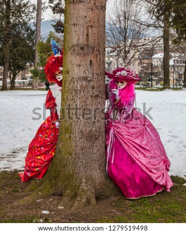 Annecy, France, February 23, 2013:Two disguised persons playing hide-and-seek near a tree trunk in a forest in Annecy, during a Venetian Carnival which is held yearly #1279519498