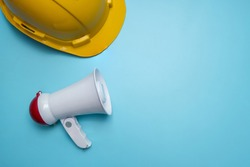 Announcement and announce advertising background public relations about construction building, home, house and real estate with megaphone and yellow helmet on blue background, copy space