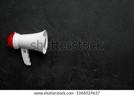 Announcement concept. Megaphone on black background top view copy space
