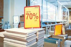Announcement of seventy percent discounts on ceramic tiles in a finishing materials store.