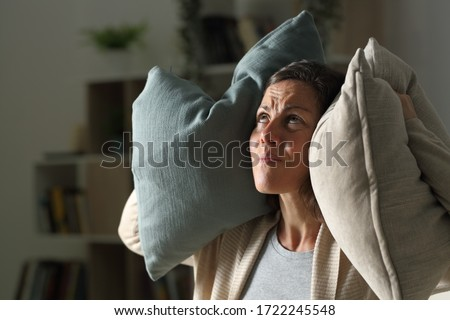 Annoyed adult woman suffering neighbour noise in the livingroom at night at home