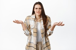 Annoyed and confused woman cant understand wtf happening, shrugging shoulders and grimacing at something ridiculous and stupid, dont know nothing, standing careless against white background