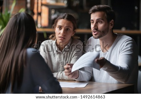 Annoyed angry disappointed customers clients couple holding paper arguing with bank manager fight complain on bad contract terms high mortgage rate demand claim insurance compensation meeting lawyer