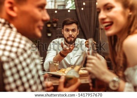 Photo of  Annoyed bored man. Handsome short-haired nice-appealing young-adult annoyed bored man holding a burger and feeling lonely while his friends are flirting with each other