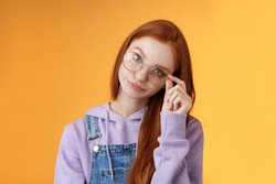 Annoyed bossy unimpressed bothered young redhead female coworker smirking tilting head irritated touch glasses look ignorant cringing stupid uninteresting doubtful story not buy any excuses