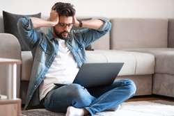 Annoyed caucasian young bearded man with eyeglasses and dressed casual sitting on floor with laptop in lap, holding head and getting nervous about situation on his bank account.