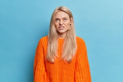 Annoyed dissatisfied woman concentrated above smirks face and looks at something with aversion has long blonde hair dressed in knitted orange jumper isolated over blue wall. Negative face expressions