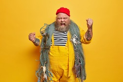 Annoyed emotional male sailor or professional seaman has sea cruise poses with fishing net raises tattooed arms and yells outraged wears red hat and yellow overalls stands indoor. Marine life concept