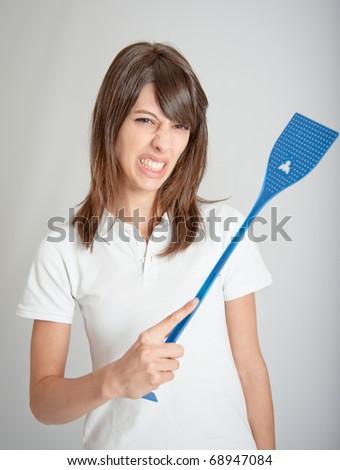 Annoyed girl holding a flyswatter