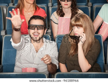 Annoyed girl with date reaching out with 3D glasses