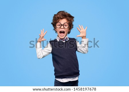 Annoyed little genius in school uniform and glasses screaming and gesturing with hands against blue background