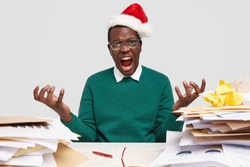 Annoyed male spreads palms, feels irritated as works during holidays, has to analyze many papers, wears Santa Claus headgear, green sweater, exclaims with exasperation and anger, sits at work place