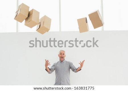 Annoyed mature man with falling boxes standing against white background
