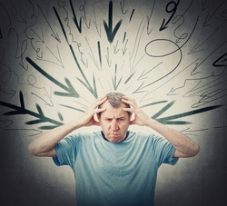 Annoyed middle aged man keeps hands to head, feels headache being under pressure as multiple arrows points negativity towards him. Frustrated and fatigued senior person. High tension, dismay concept