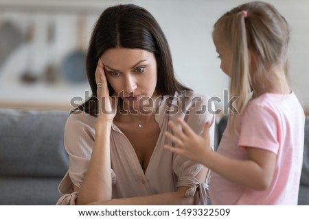 Annoyed mom and restless little daughter at home, mother sitting on couch touch head or temples feels headache due to noisy kid standing near her, tired parent of difficult hyperactive child concept
