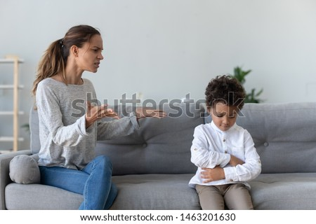 Annoyed serious mom scolding lecturing stubborn african kid son for bad behavior at home, angry parent mother punish little mixed race guilty child boy demand discipline, family conflicts concept ストックフォト ©