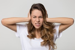 Annoyed stressed woman cover ears feel hurt ear ache pain otitis suffer from loud noise sound headache, irritated stubborn girl deaf hear not listen to noisy music isolated on white studio background