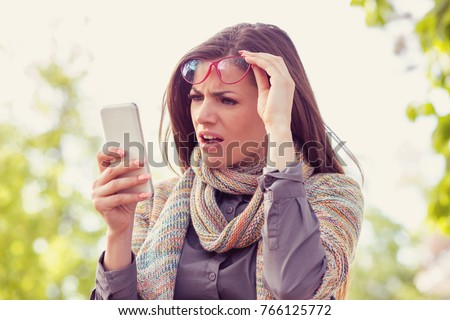 Annoyed upset woman in glasses looking at her smart phone with frustration while walking on a street on an autumn day   #766125772