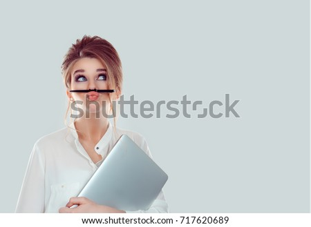 Annoyed woman, funny student with laptop computer playing holding pen between nose and lips as mustache looking up thinking playful bored after working long hours isolated light blue white background