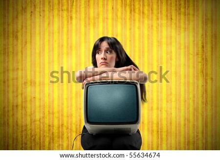 Annoyed woman holding an old television on her knees