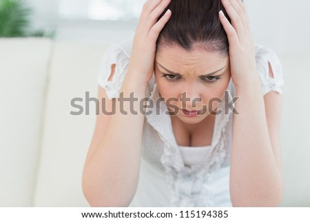 Annoyed woman sitting on the couch in the living room and holding her head in her hands