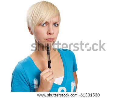 Annoyed woman taps at her chin with a pen