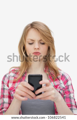 Annoyed woman using a mobile phone against a white background