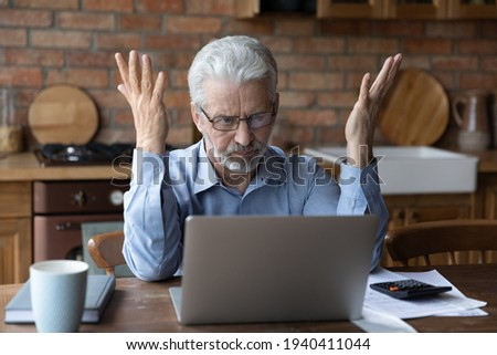 Annoyed worried aged man pensioner sit by laptop unable to make utility bill loan payment online has question how to use app need help. Stressed old grandpa confused with unexpected debt on pc screen