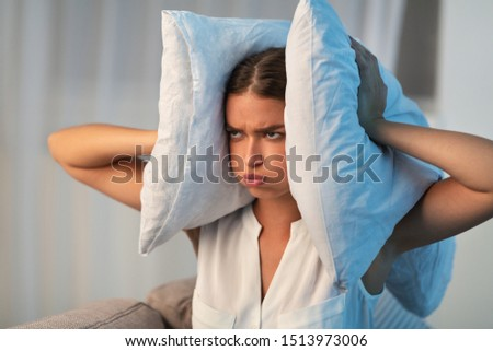 Annoyed Young Lady Covering Ears With Pillow Irritated Because Of Noise At Home. Bad Sound Insulation.