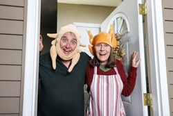 Annoying in laws wearing turkey hats welcoming family on the holiday