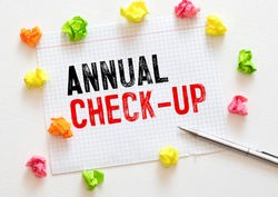 Annual check-up text on paper with blue dumbbell, stethoscope, spectacles, measurement tape and delicious green apple on wooden table - medical, health and disease concept