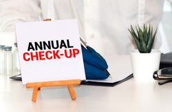 Annual Check-up text on paper with heart beat diagram, stethoscope, delicious green apple, measurement tape and blue dumbbell on wooden table - medical, health and disease concept