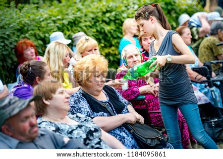 Annual city picnic for people with special needs Cerebral palsy July 19, 2017 in Bila Tserkva, Ukraine. Volunteer distributes food and drinks to the elderly and disabled in wheelchairs #1184095861