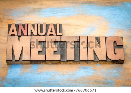 annual meeting word abstract in letterpress wood type against grunge wooden background