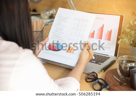 Annual report (cover,summary report,financial,paper,document,graph,news) review by Working and business woman or journalist.Brochure design with laptop on table.Business woman and journalist concept.