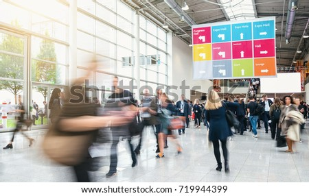 Anonymous blurred business people rushing in a hall of a trade f